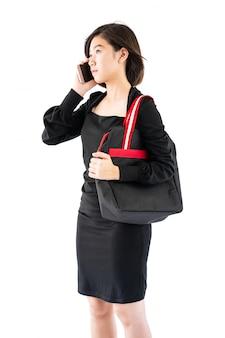 Vrouw die een zwarte het winkelen zak draagt die cellphone gebruikt