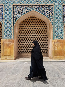 Vrouw die een zwarte hiqab draagt in de deur van een moslimmoskee in iran