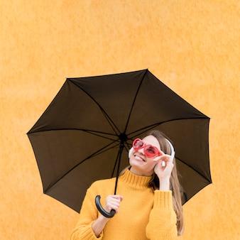 Vrouw die een zwarte paraplu houdt