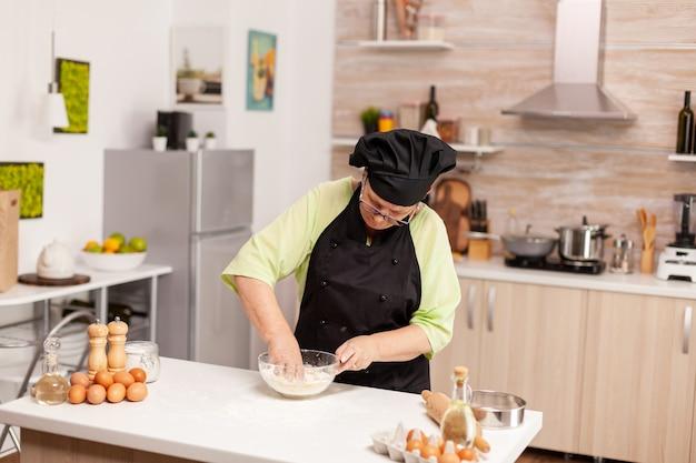 Vrouw die eieren met bloem mengt om deeg te maken volgens traditioneel recept op keukentafel