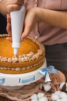 Vrouw die eigengemaakte cake verfraait