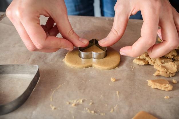 Vrouw die eigengemaakte gemberkoekjes in de vorm van harten op een houten lijst maakt.