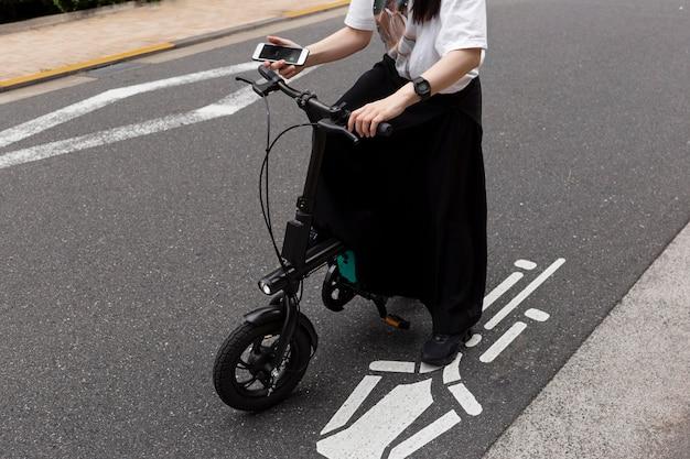 Vrouw die elektrische fiets in de stad berijdt en smartphone houdt