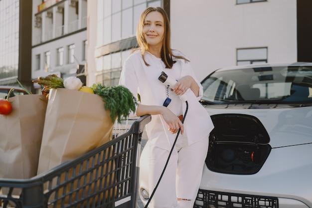 Vrouw die elektro auto laadt bij het elektrische benzinestation