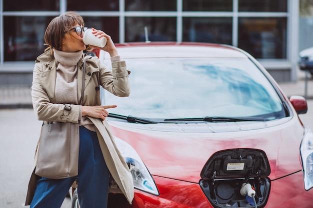 Vrouw die elektroauto laadt bij het elektrische benzinestation en koffie drinkt