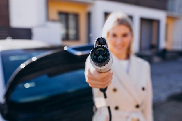 Vrouw die elektroauto laden door haar huis en lader houden