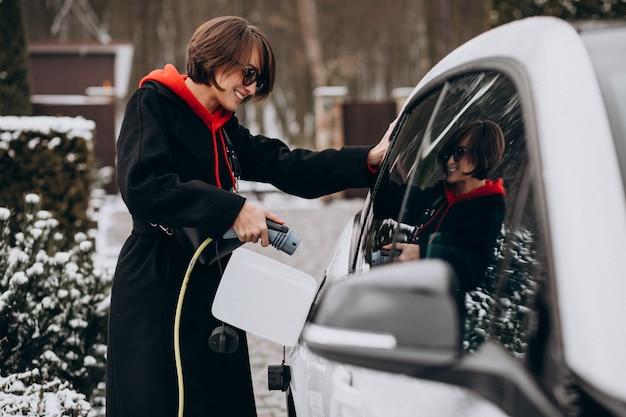Vrouw die elektroauto laden door haar huis