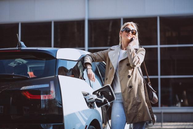 Vrouw die elektrocar laadt bij het elektrische benzinestation