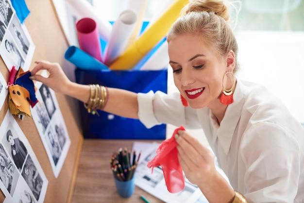 Vrouw die elk kleurrijk materiaal vergelijkt