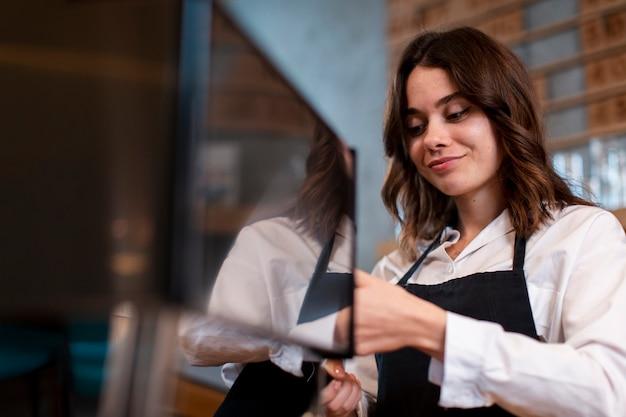 Vrouw die en aan koffiemachine glimlacht werkt