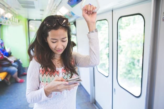 Vrouw die en berichten doorbladert typt in een openbare bus