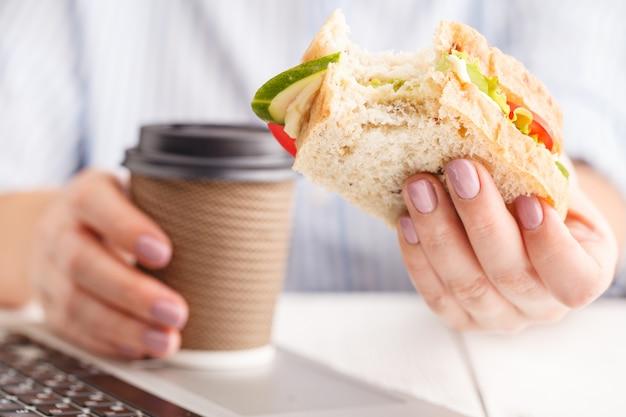 Vrouw die en bij bureau werkt eet