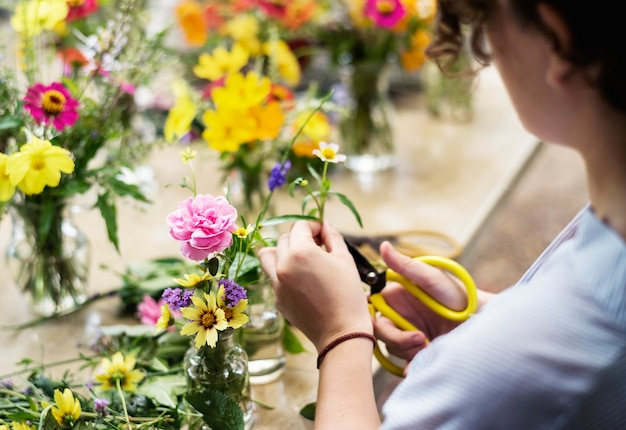 Vrouw die en bloemen voorbereidt schikt