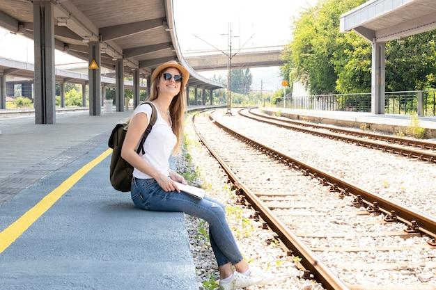 Vrouw die en de trein glimlacht zoekt