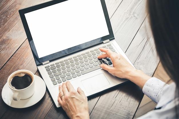 Vrouw die en door laptop in bureau typt zoekt. ruimte in scherm voor tekst.