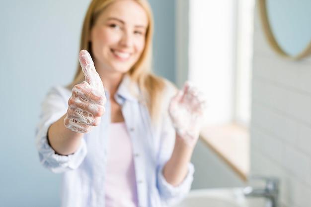 Vrouw die en duimen knipogen tonen terwijl het wassen van handen
