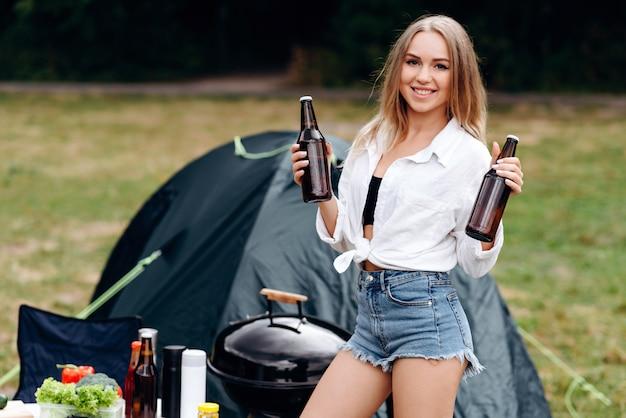 Vrouw die en een bier in het kamperen bevinden zich houden