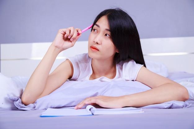 Vrouw die en een boek op haar bed in slaapkamer denkt schrijft