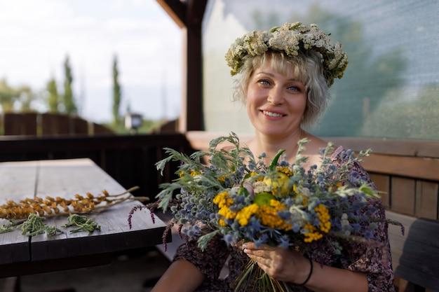 Vrouw die en een boeket van wilde bloemen zit houdt