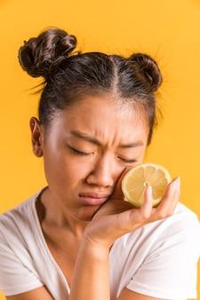 Vrouw die en een citroen fronst houdt