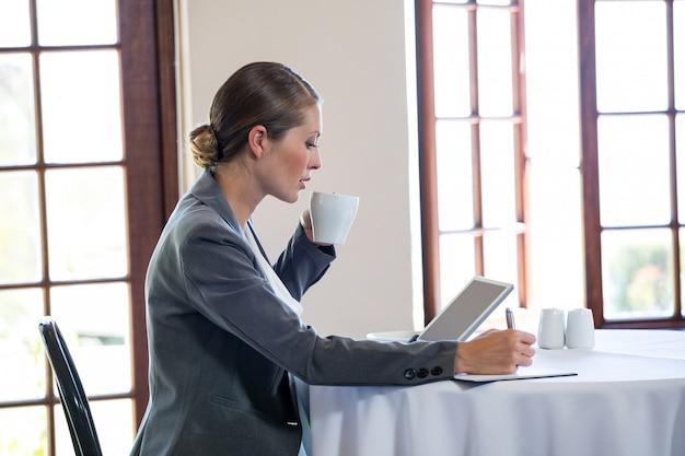 Vrouw die en een koffie werkt drinkt