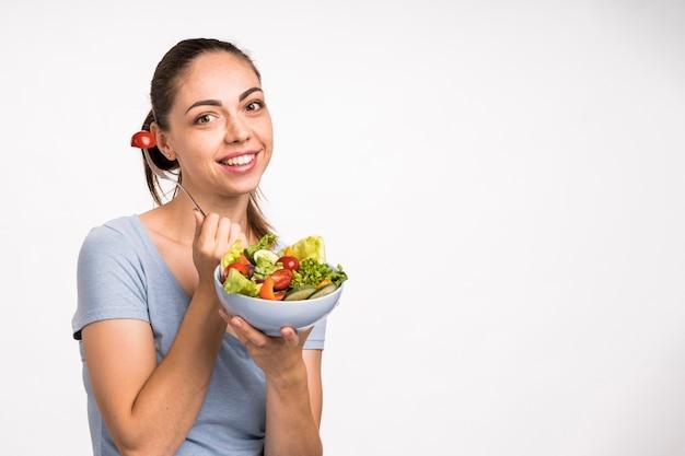 Vrouw die en een ruimte van het saladeexemplaar glimlacht houdt