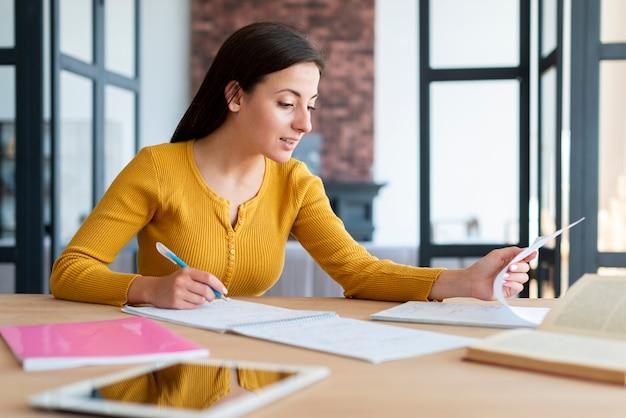 Vrouw die en haar nota's werkt controleert