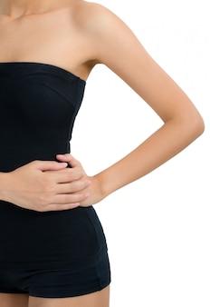 Vrouw die en haar taille in pijngebied houdt masseert dat op wit wordt geïsoleerd