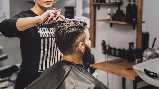 Vrouw die en haircutting mens kammen