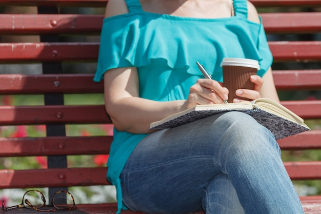 Vrouw die en in een park bestudeert schrijft
