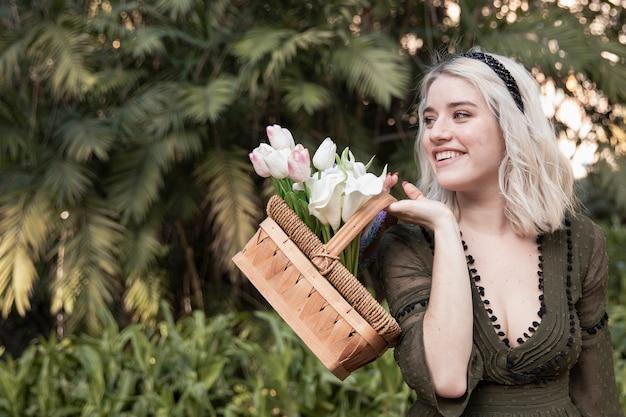 Vrouw die en met mand van bloemen glimlacht stelt