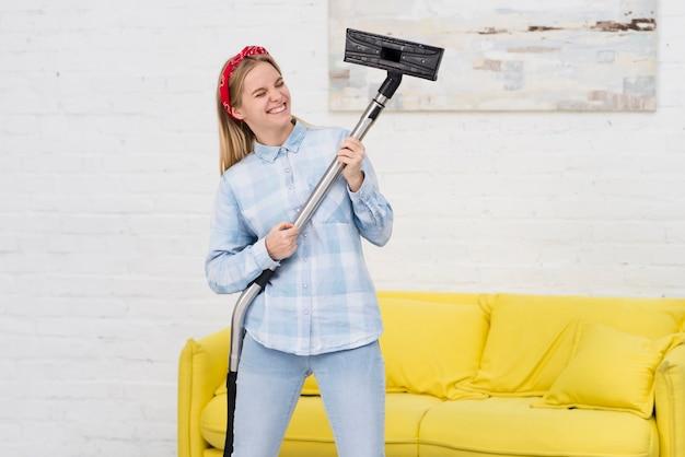 Vrouw die en met vacuüm schoonmaakt speelt