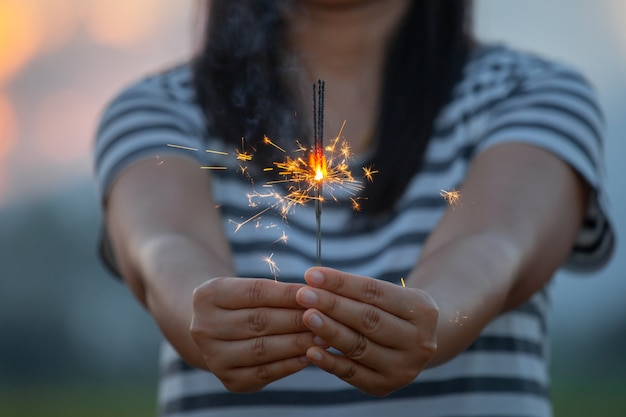 Vrouw die en met vuursterretjes op het festival in het padieveld houden houden in zonsondergangtijd