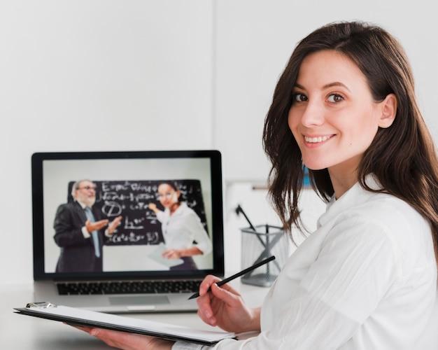 Vrouw die en online van laptop glimlacht leert