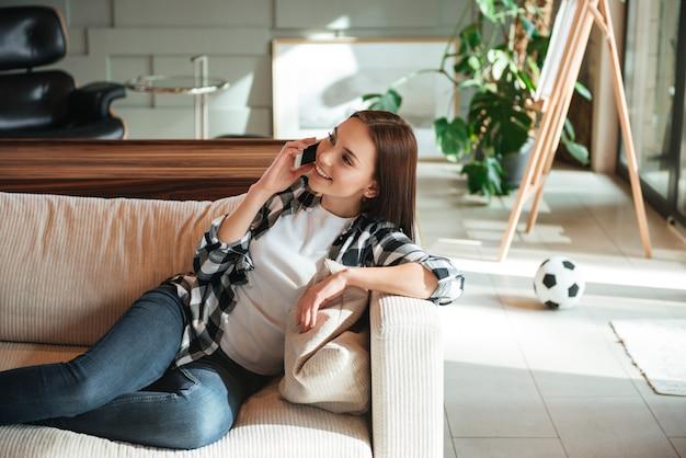 Vrouw die en op telefoon glimlacht spreekt