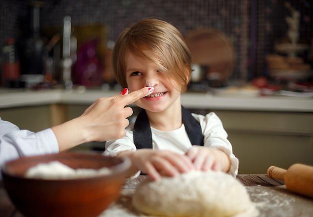 Vrouw die en pret met meisje kookt heeft