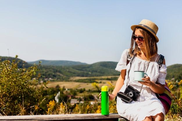 Vrouw die en van een koffie zit geniet