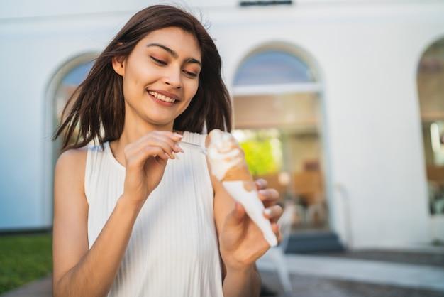 Vrouw die en van een roomijs geniet eet.