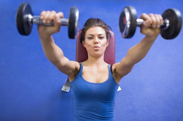 Vrouw die energetisch gewichten opheft