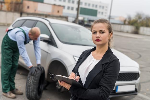Vrouw die enkele documenten over autoservice invult