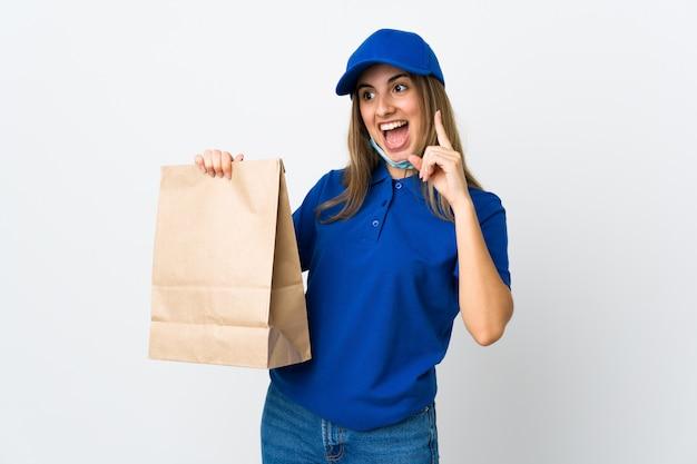 Vrouw die eten bezorgt en beschermt tegen het coronavirus met een masker over een geïsoleerde witte muur die de oplossing wil realiseren terwijl ze een vinger opheft