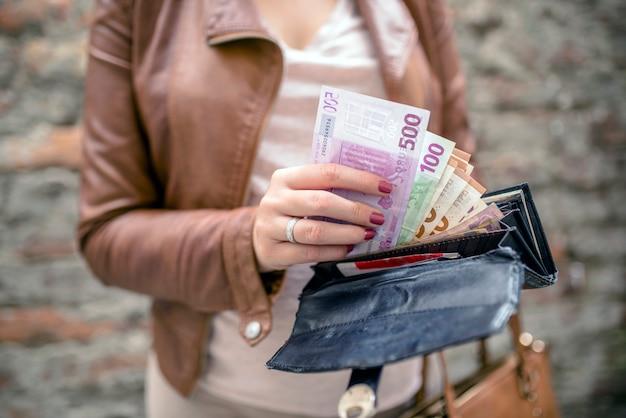 Vrouw die euro geld van zwarte portefeuille neemt. vrouwenhanden die europese bankbiljetten houden