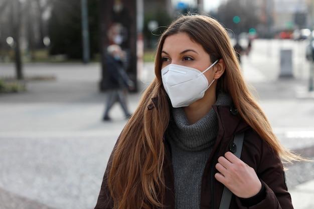 Vrouw die ffp2 kn95 gezichtsmasker in winterkleren buiten draagt