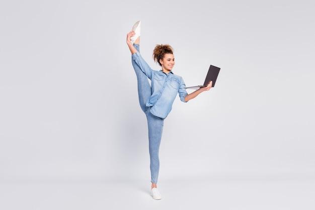 Vrouw die flexibele lichaamsvaardigheden toont die laptop houden
