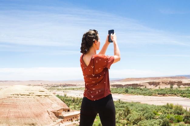 Vrouw die foto in woestijnlandschap van erachter neemt