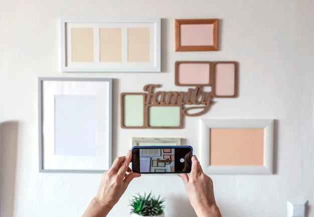 Vrouw die foto maakt van witte muur met set van verschillende lege verticale en horizontale fotolijsten, familie fotogalerijproject om moment vast te leggen, mockupsjabloon op de witte muur, levensstijl