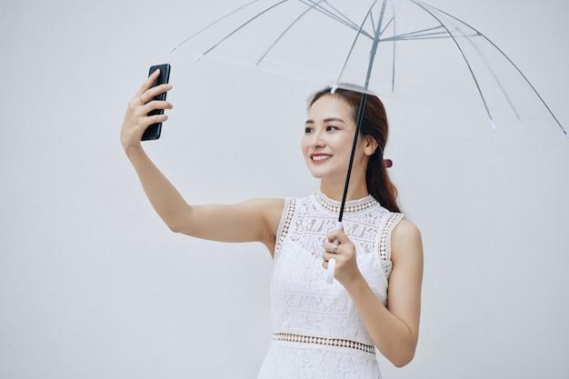 Vrouw die foto met paraplu neemt