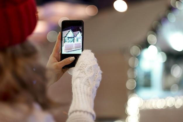 Vrouw die foto nemen aan smartphone met slingers en vakantielichten op feestelijke kerstmis of nieuwjaarmarkt.