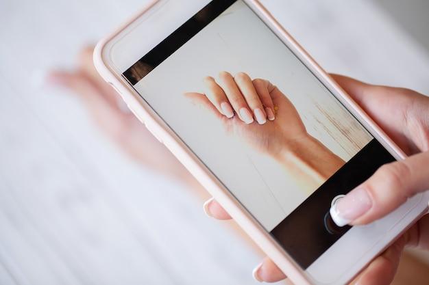 Vrouw die foto nieuwe manicure op camera haar telefoon maakt.