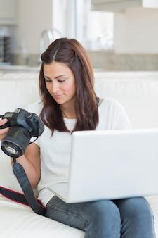 Vrouw die foto's bekijkt terwijl het houden van laptop